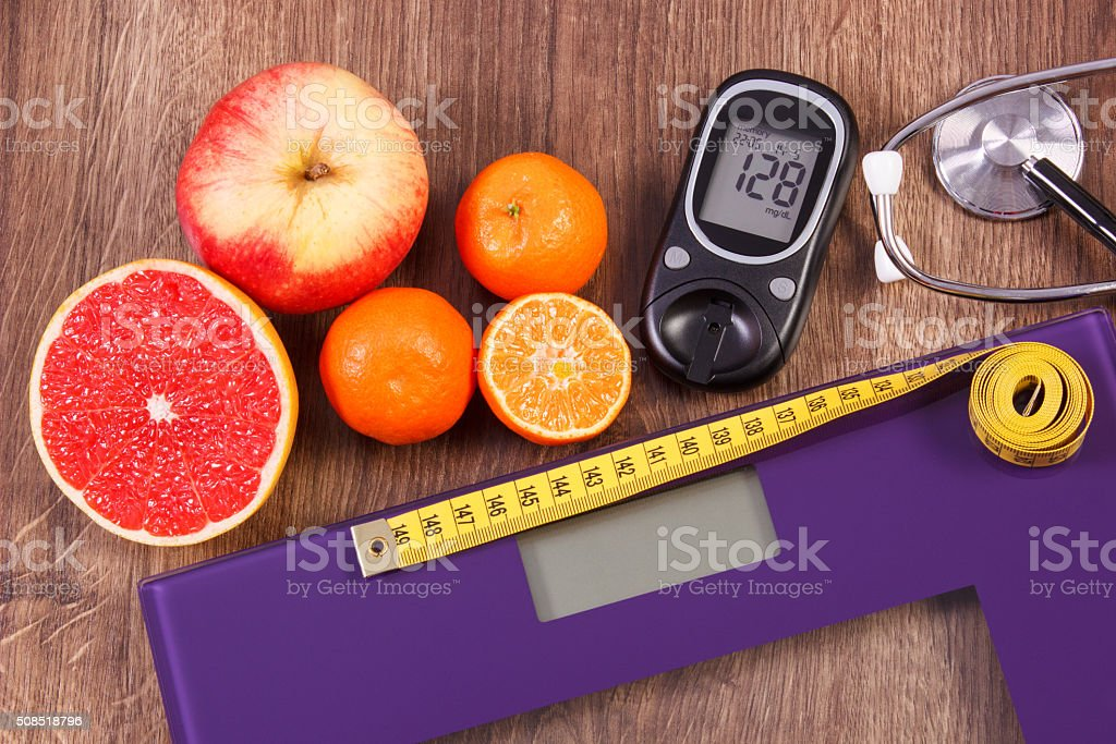 Electronic bathroom scale and glucometer, stethoscope and healthy food stock photo