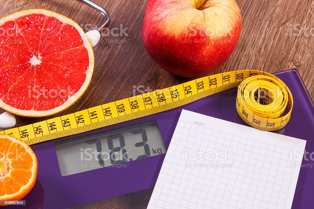 Electronic bathroom scale, centimeter and fresh fruits with stethoscope stock photo
