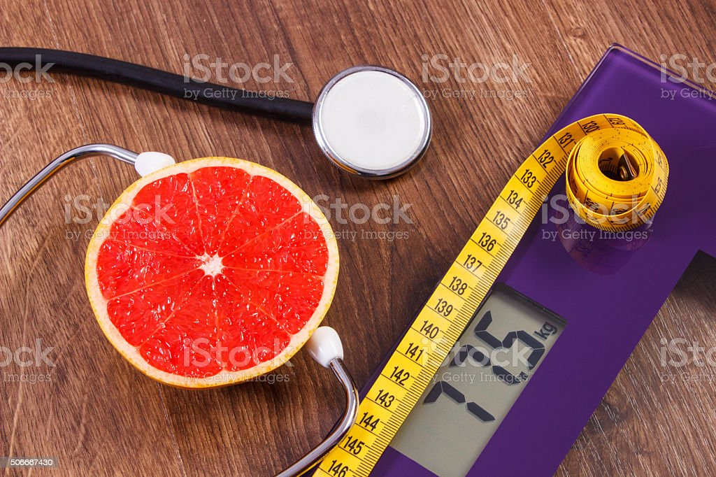 Electronic bathroom scale, centimeter and fresh grapefruit with stethoscope stock photo