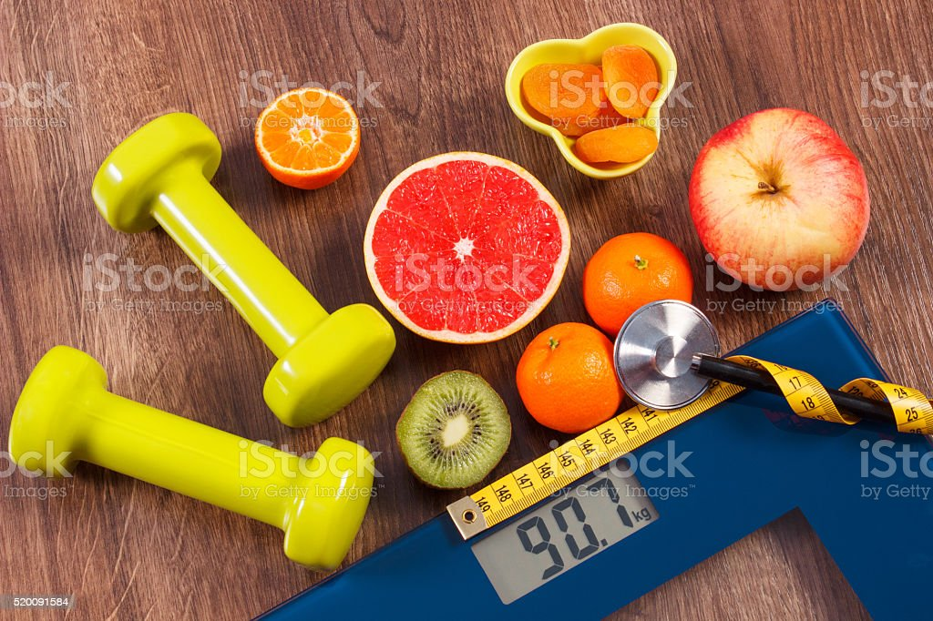 Electronic bathroom scale, centimeter and stethoscope, fresh fruits, dumbbells stock photo