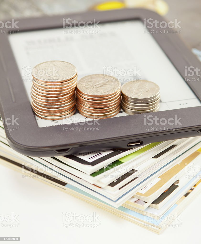 Electronic book reader with bars of coins royalty-free stock photo