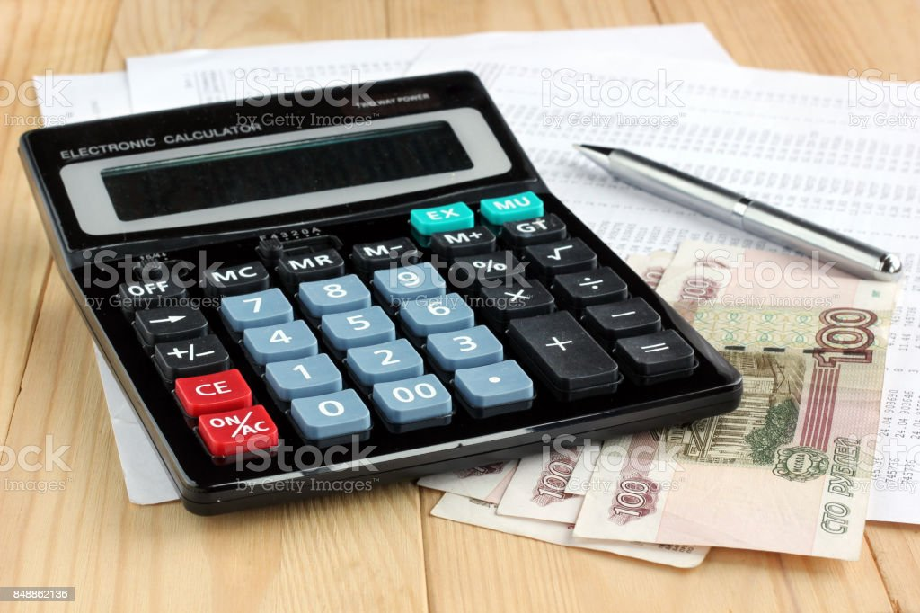 Electronic calculator, pen and Russian money on sheets of paper with numbers. stock photo
