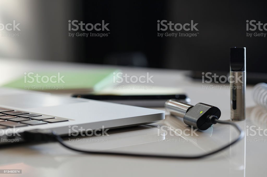 Electronic cigarette charging on a laptop stock photo