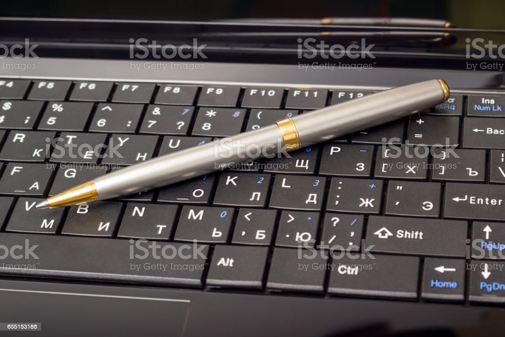 Electronic collection - laptop keyboard with pen stock photo