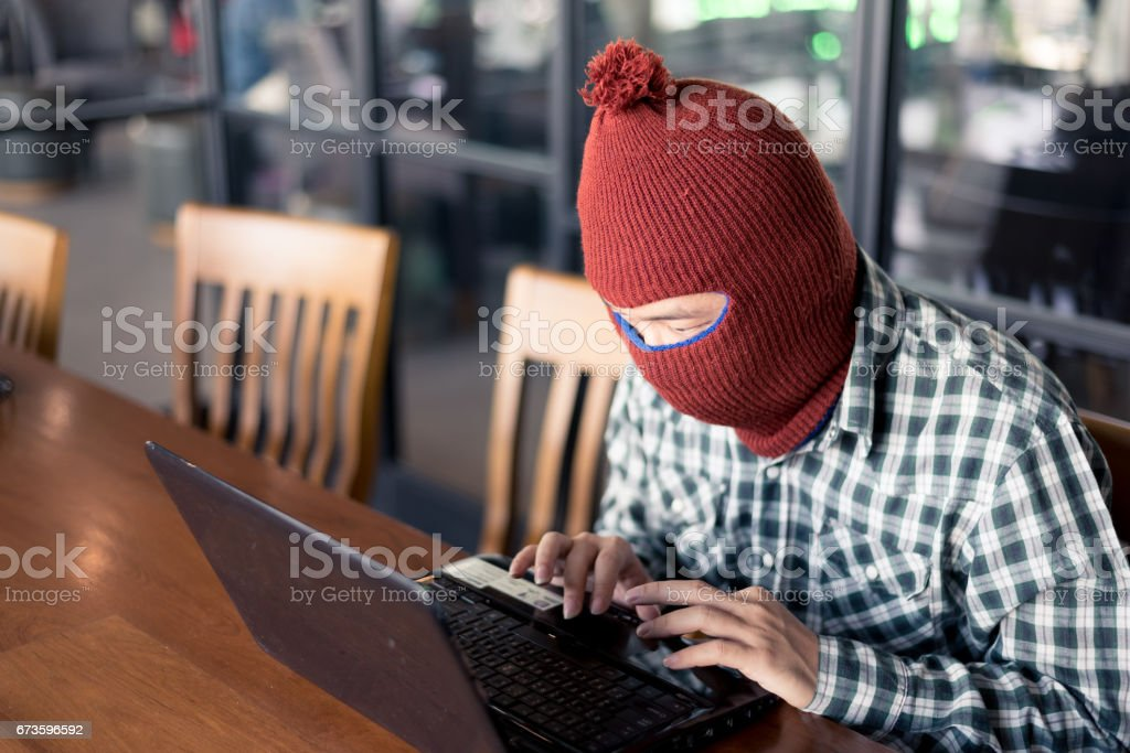 electronic crime concept. hacker is using computer. stock photo