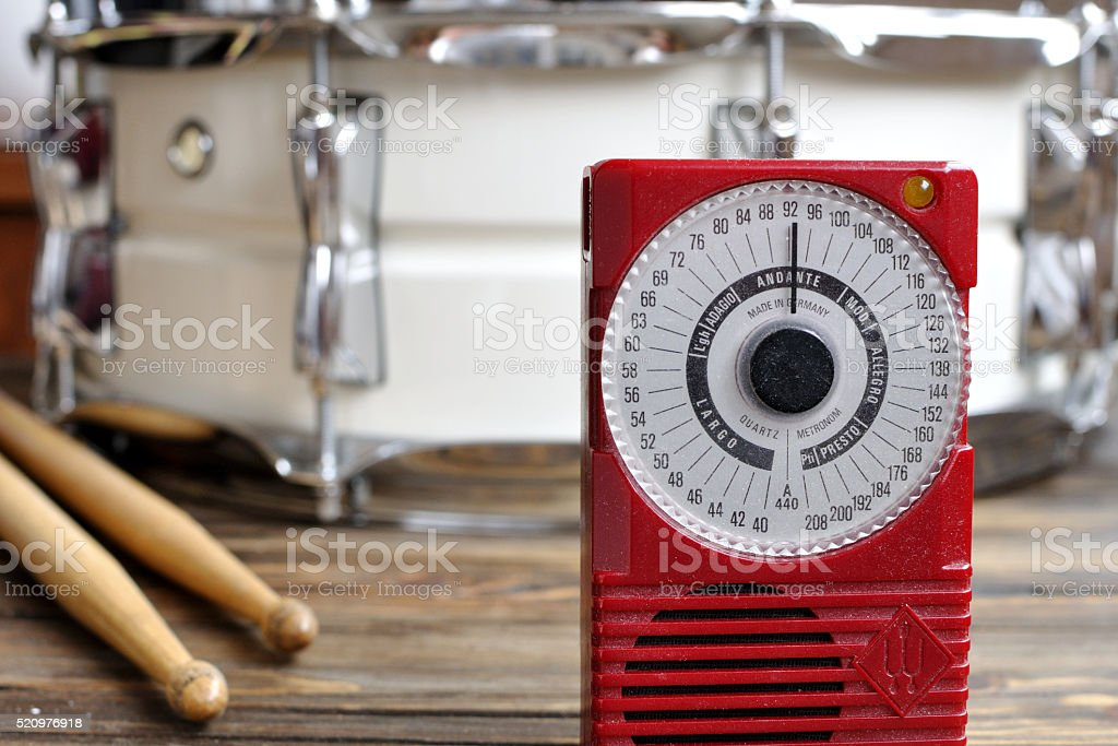 Electronic metronome with snare drum and sticks on background stock photo