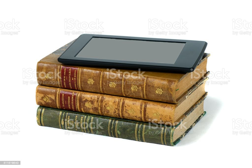 Electronic reader on a pile of books stock photo