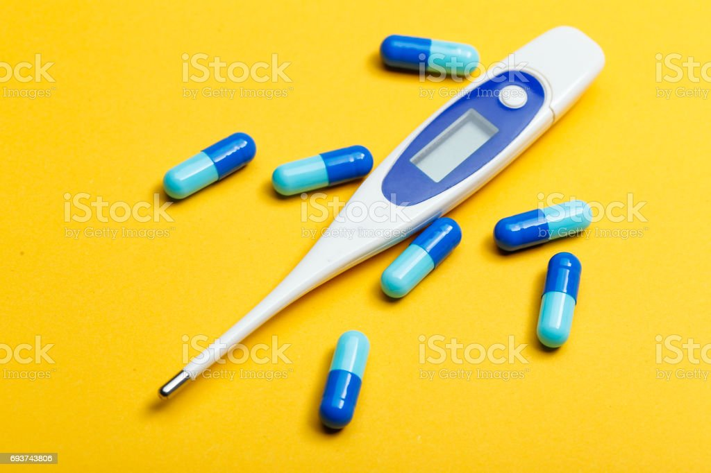 electronic thermometer and blue capsules on yellow background stock photo