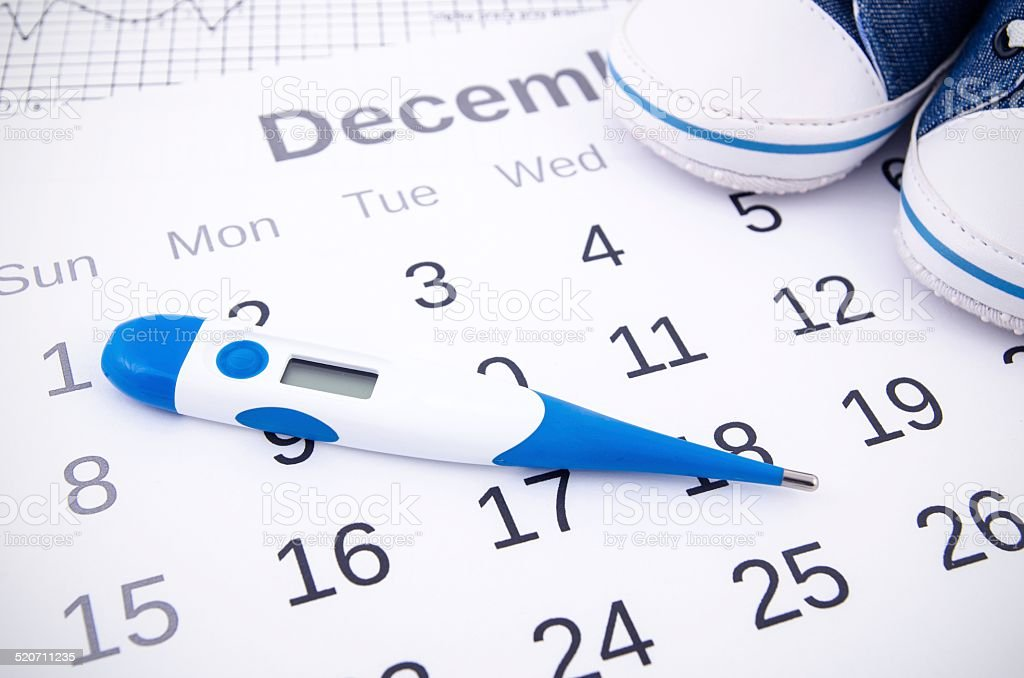 Electronic thermometer in fertility concept on calendar stock photo