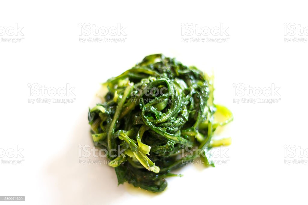 Elegance: Cooked Greens Dressed with Oil on White Plate/Background stock photo