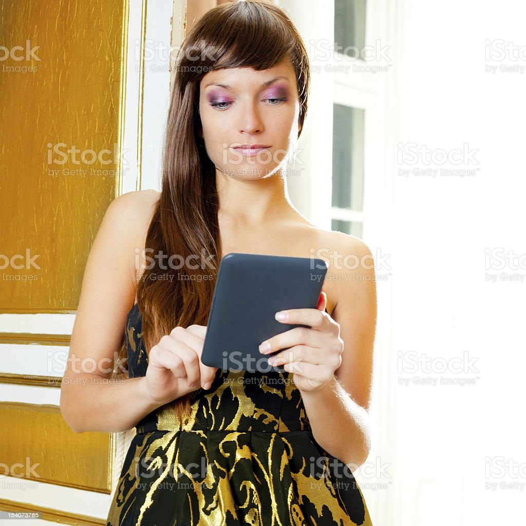 elegance fashion woman reading ebook tablet in a door royalty-free stock photo