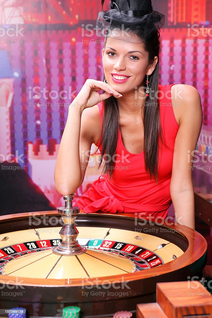 Elegance woman in red dress sitting near roulette. stock photo