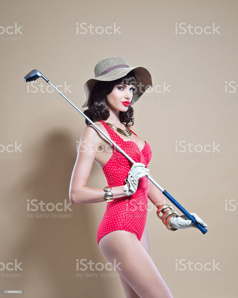 Elegance young woman wearing swimwear and sunhat holding golf stick stock photo