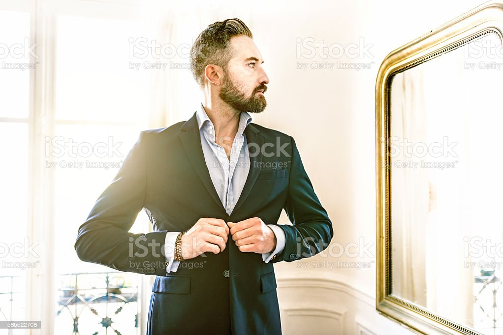 elegant bearded businessman dressing suit in front of mirror stock photo