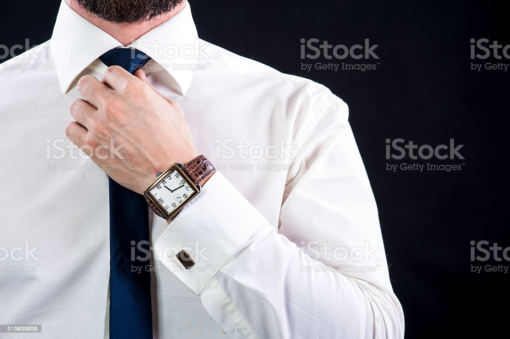 Elegant bearded man tying up his necktie stock photo