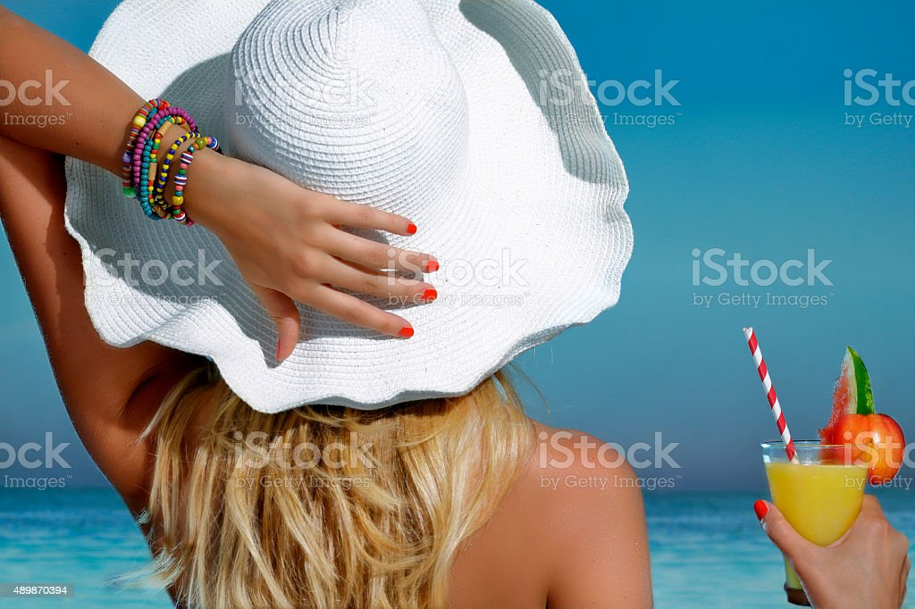 Elegant beautiful woman refreshing on the beach looking the sea stock photo