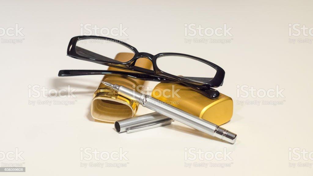 Elegant black glasses, case, metal pen. White isolate. stock photo
