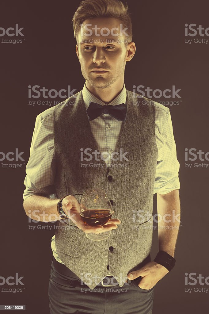 Elegant blond man in classical outfit, holding glass of cognac stock photo