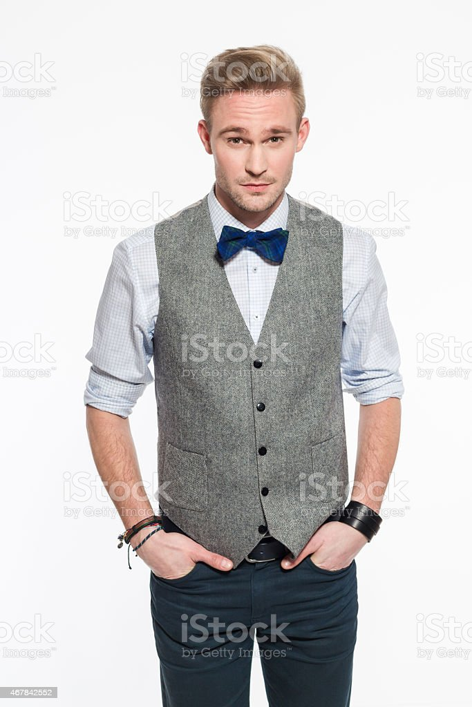 Elegant blonde young man wearing tweed vest and bow tie stock photo