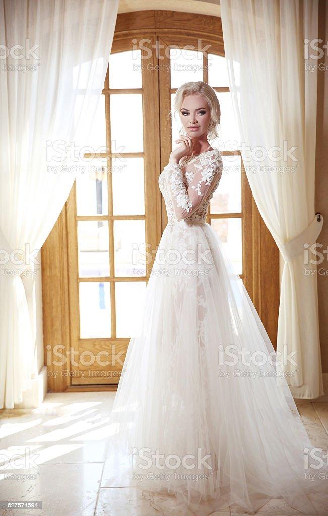 Elegant bride in fashion wedding dress. Blond woman model stock photo