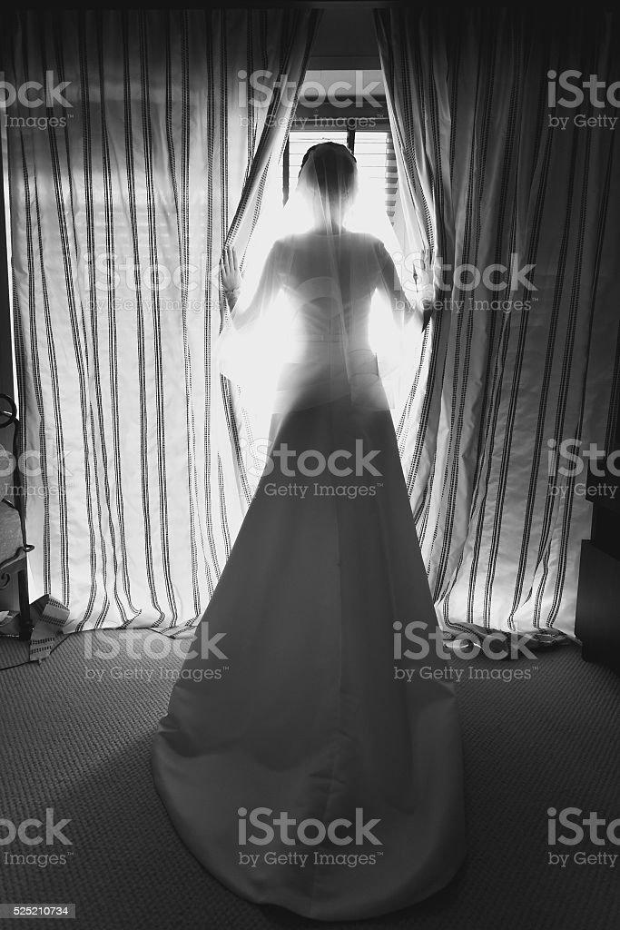 elegant bride in front of big window at hotel room stock photo