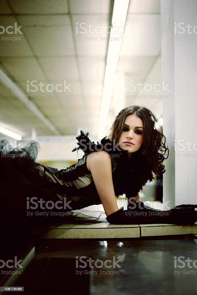 Elegant Brunette with Evening Gown and Gloves Laying on Table royalty-free stock photo