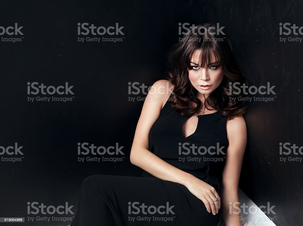 Elegant brunette woman in black dress. stock photo