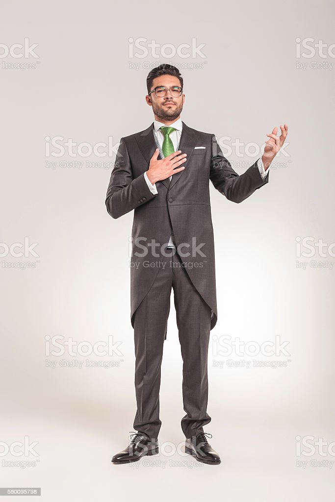 Elegant business man holding one hand on his chest stock photo