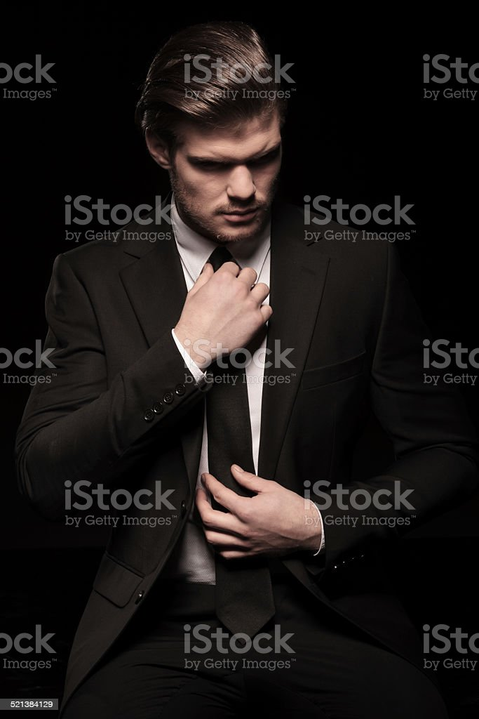 elegant business man looking down while fixing his tie stock photo