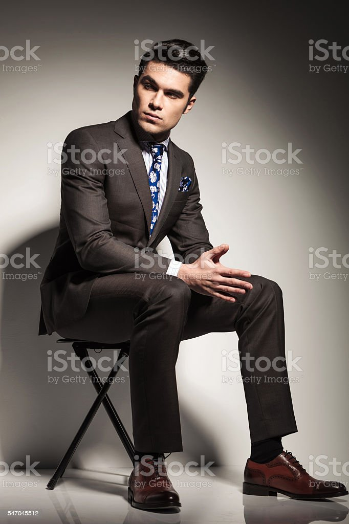 elegant business man sitting and looking to his side stock photo