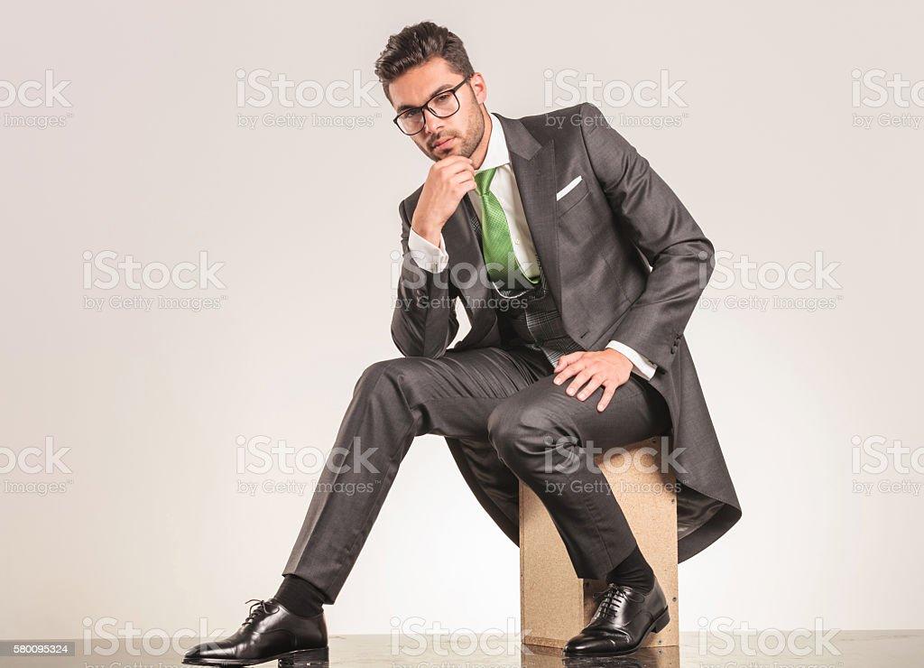 Elegant business man sitting while thinking. stock photo