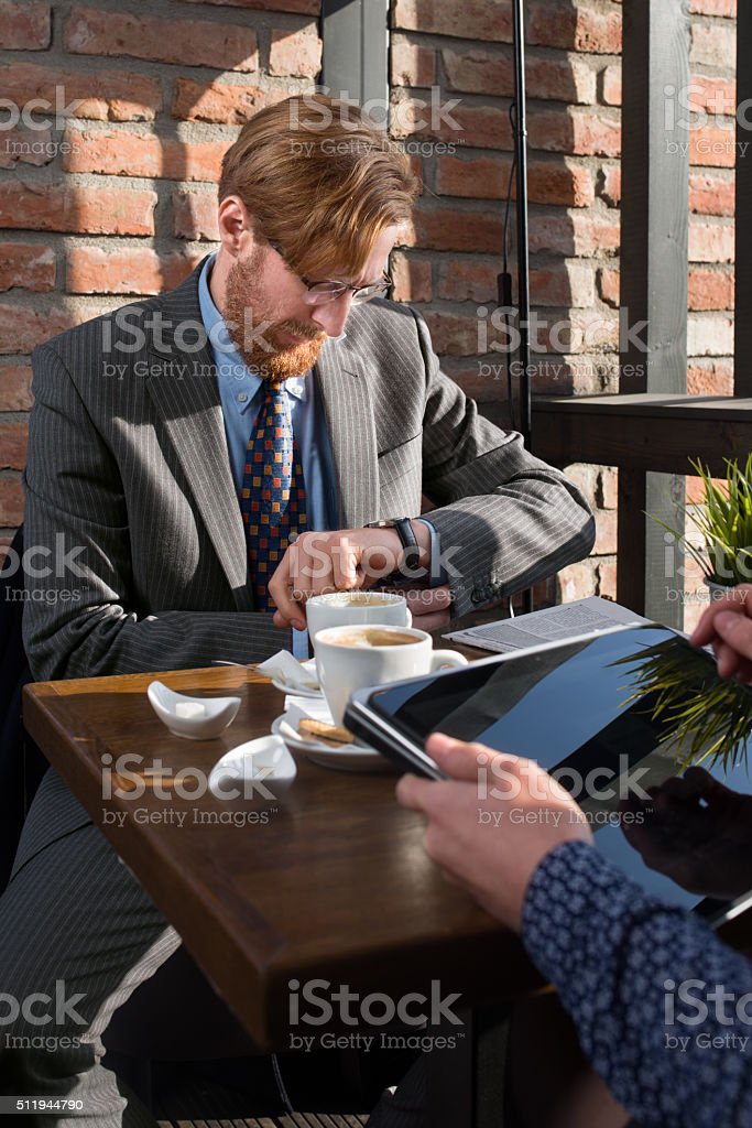 Elegant businessman having a meeting at a coffee shop stock photo