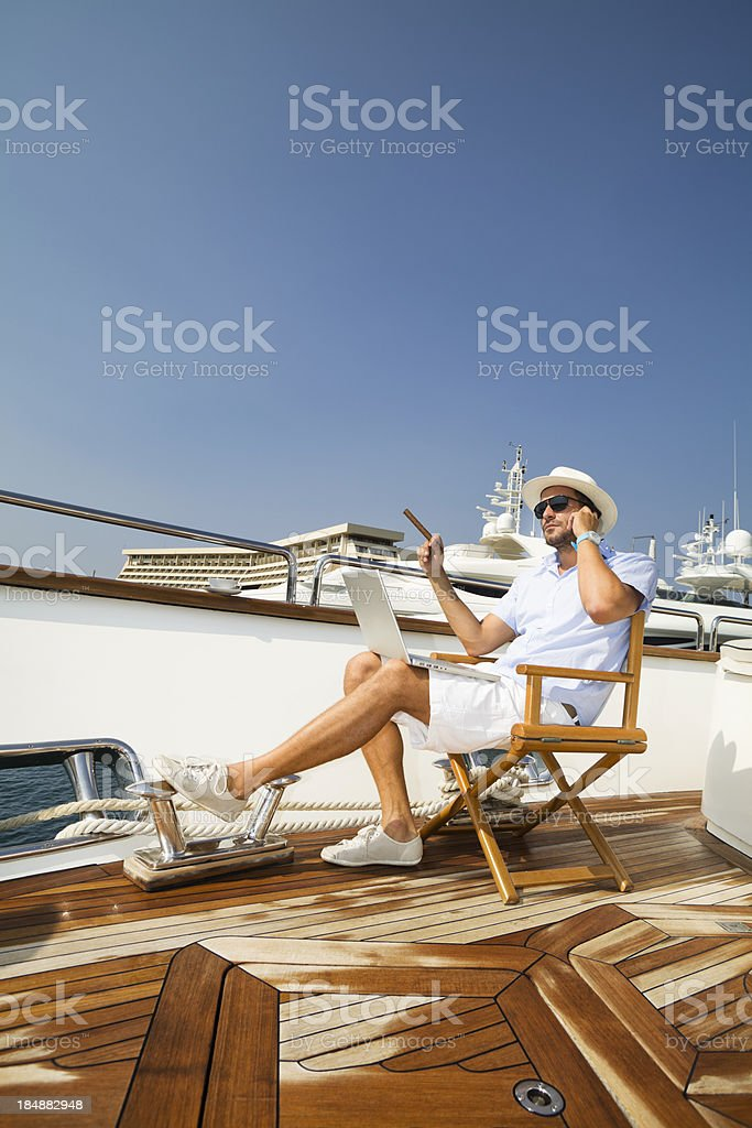 Elegant Businessman on board of the yacht. Phone conversation. royalty-free stock photo