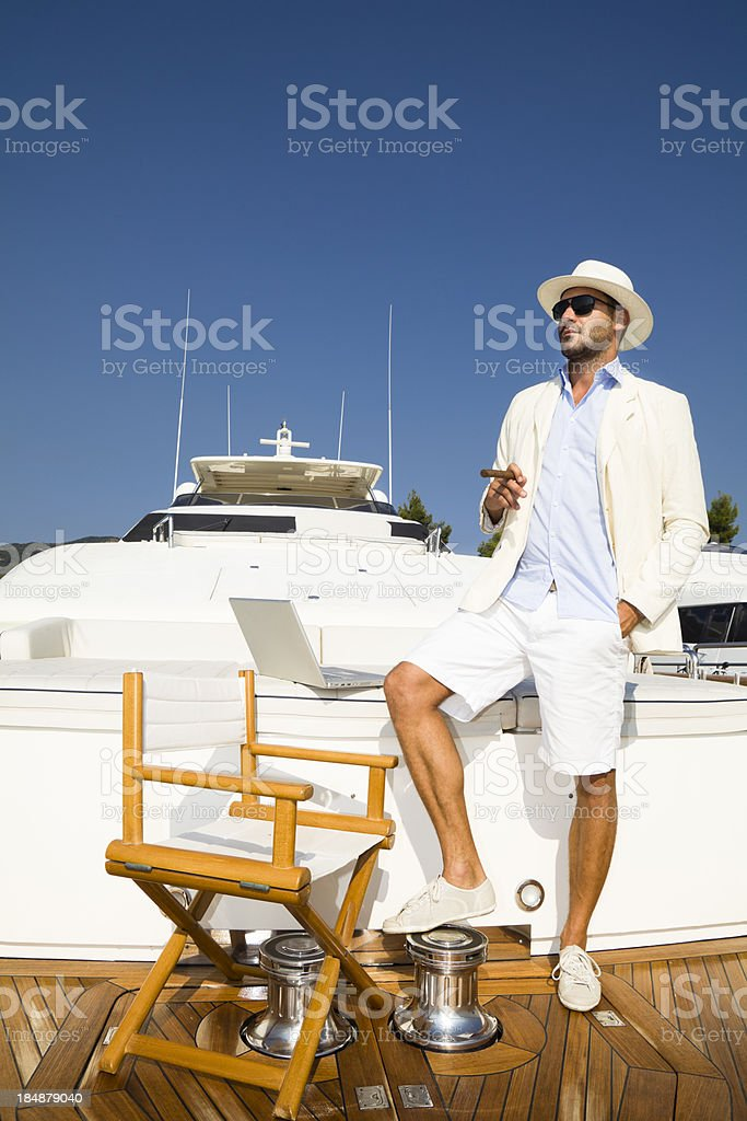 Elegant Businessman on board of the yacht relaxing with cigar stock photo
