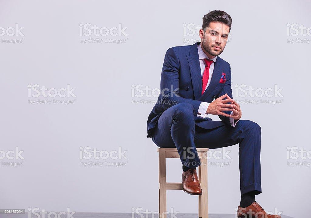 elegant businessman sitting on chair stock photo