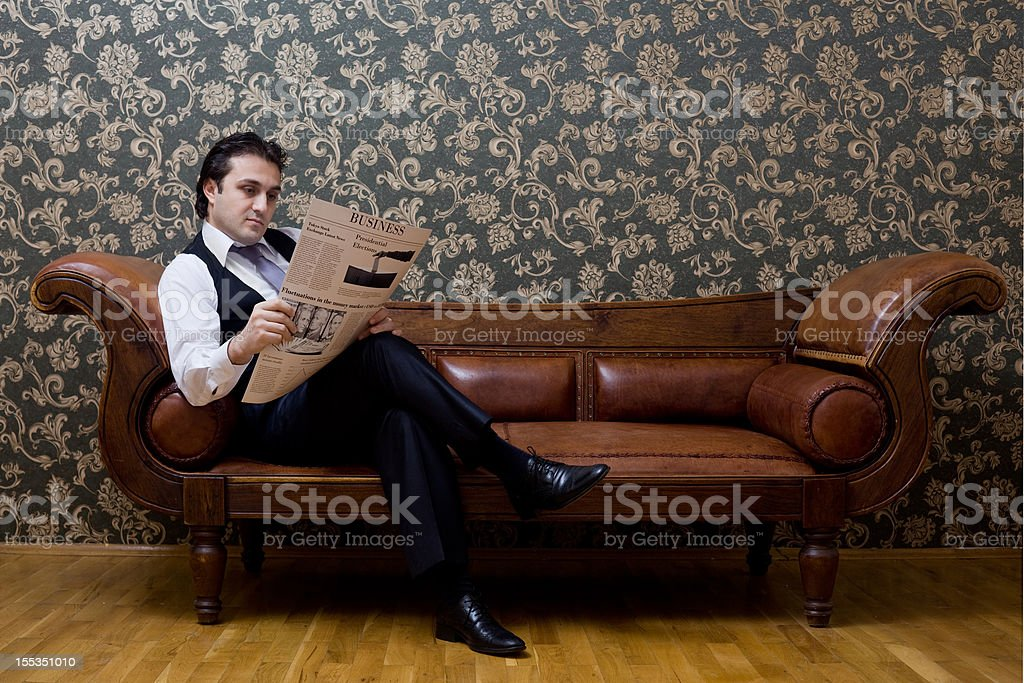 Elegant businessman sitting on sofa and reading newspaper royalty-free stock photo