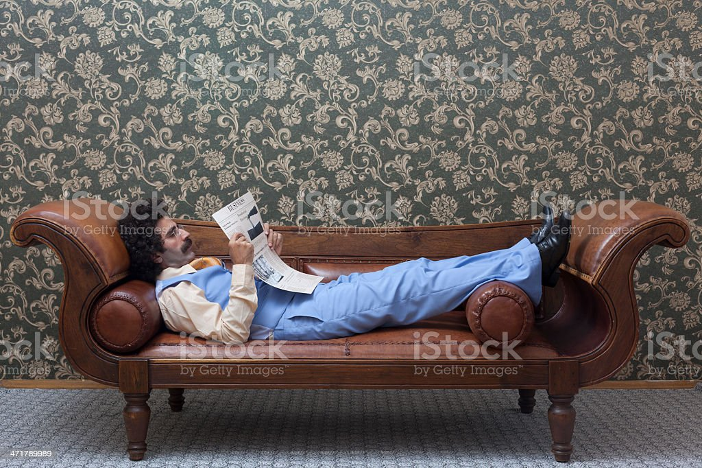 Elegant businessman sitting on sofa and reading newspaper royalty-free stock photo