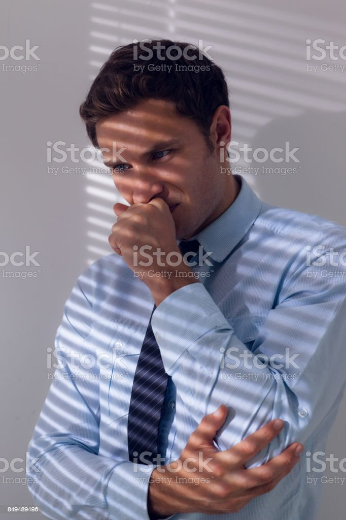 Elegant businessman with a cough against the wall stock photo