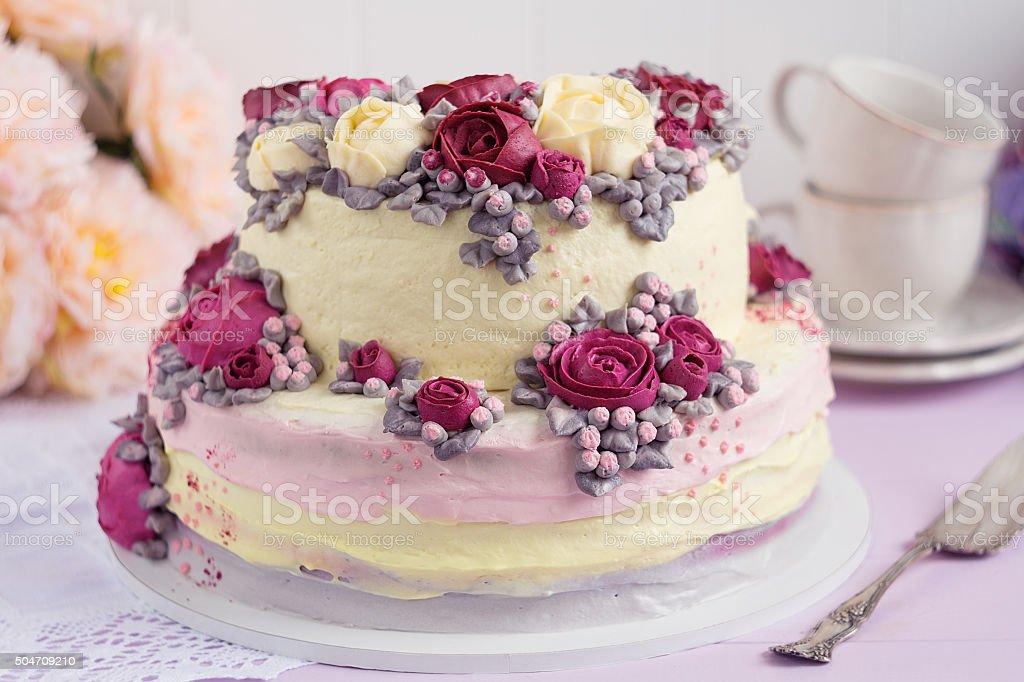 Elegant cake decorated with burgundy cream rose flowers stock photo