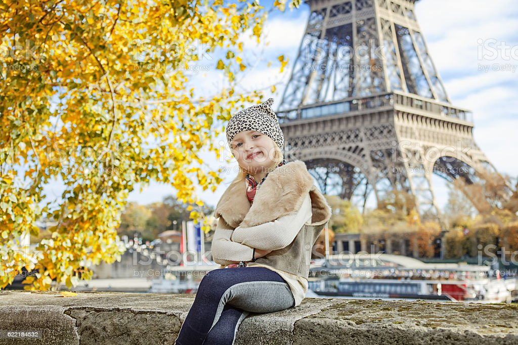 elegant child sitting on parapet near Eiffel tower stock photo