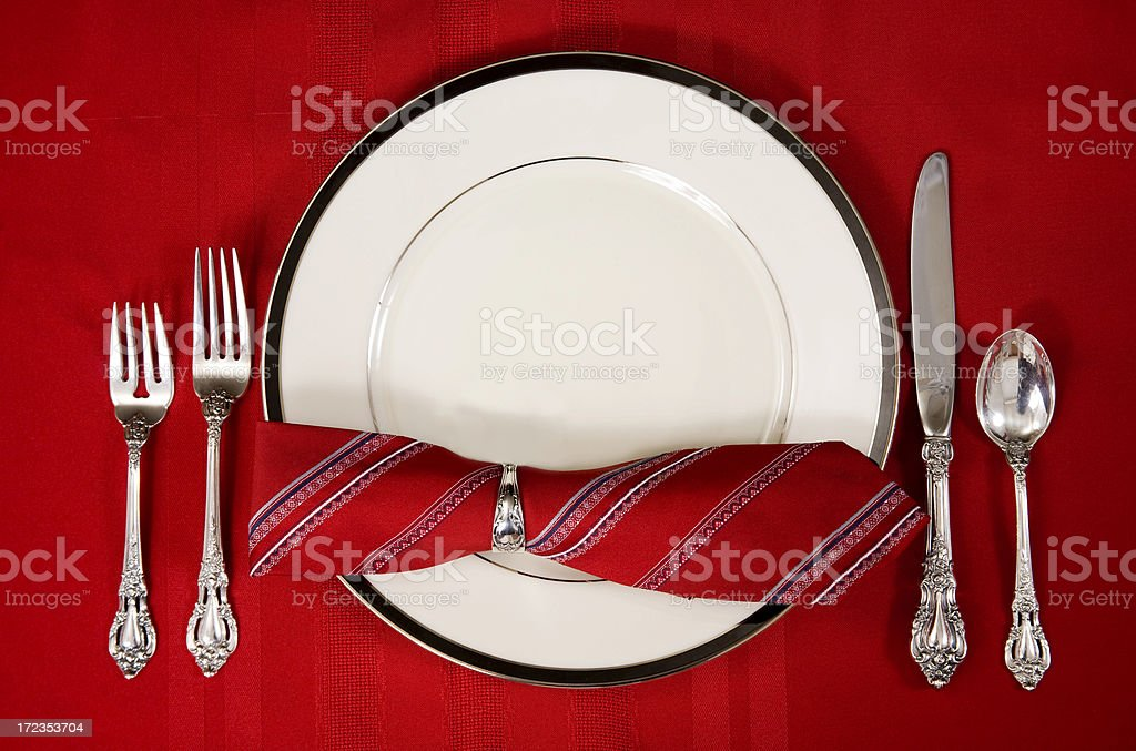 Elegant china place setting. Red tablecloth, napkin. Silverware. royalty-free stock photo