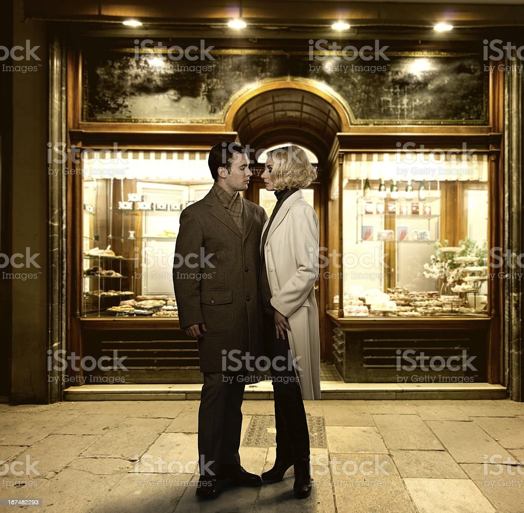 Elegant couple against bakery shop window royalty-free stock photo