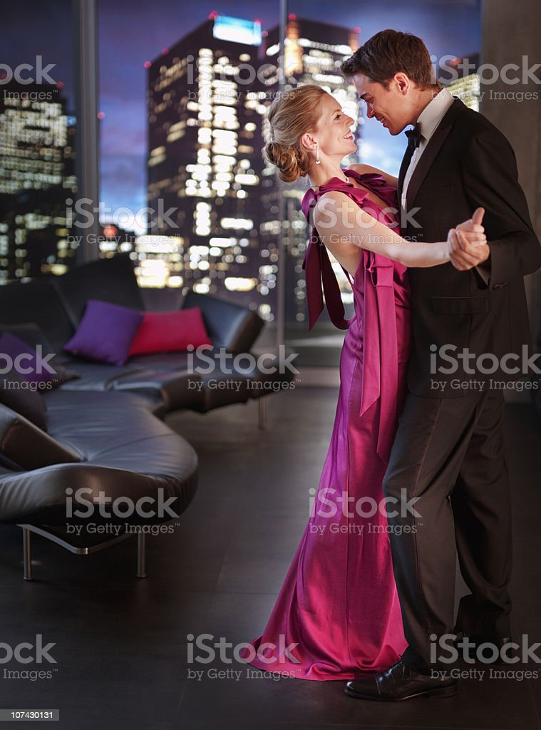 Elegant couple dancing in living room royalty-free stock photo