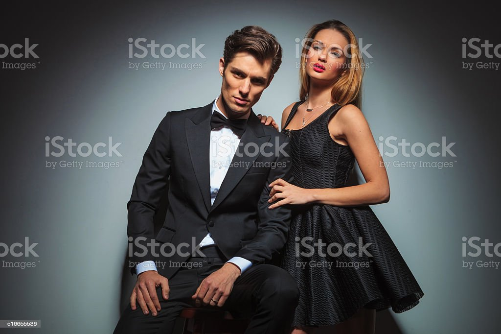 elegant couple in black posing in studio stock photo