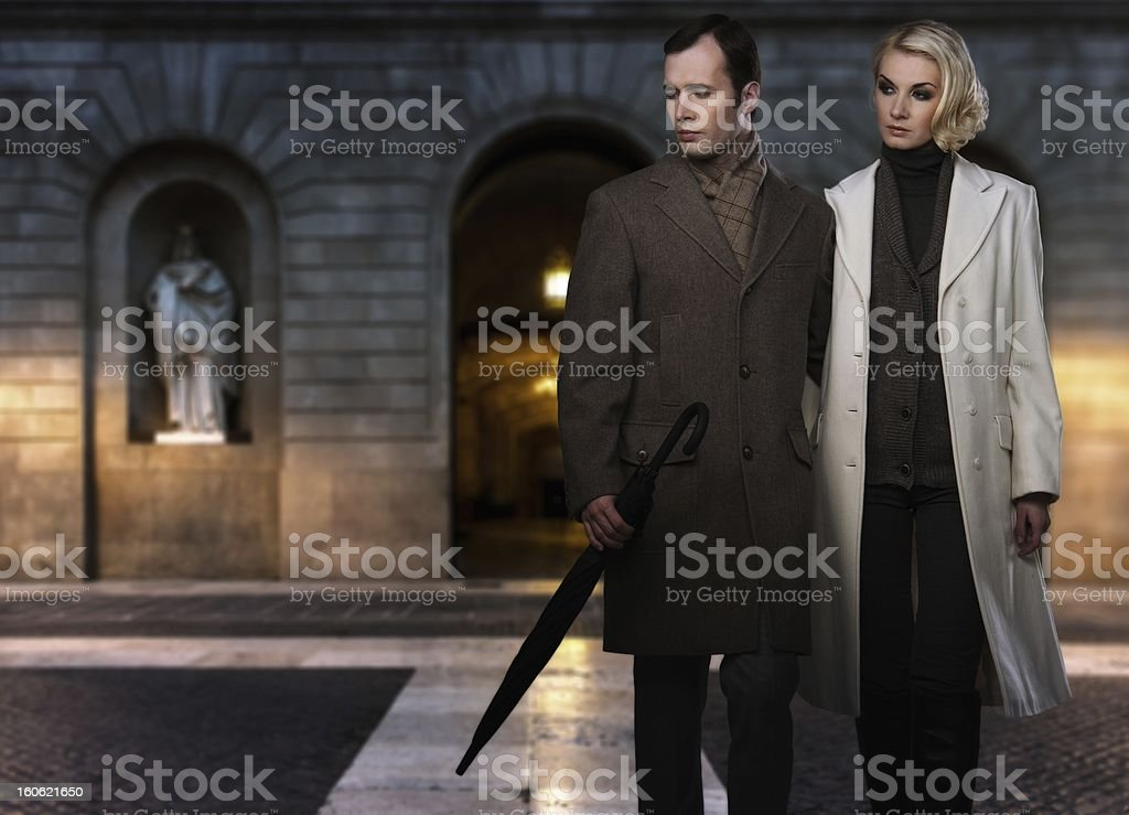 Elegant couple wearing coats against building facade in evening stock photo