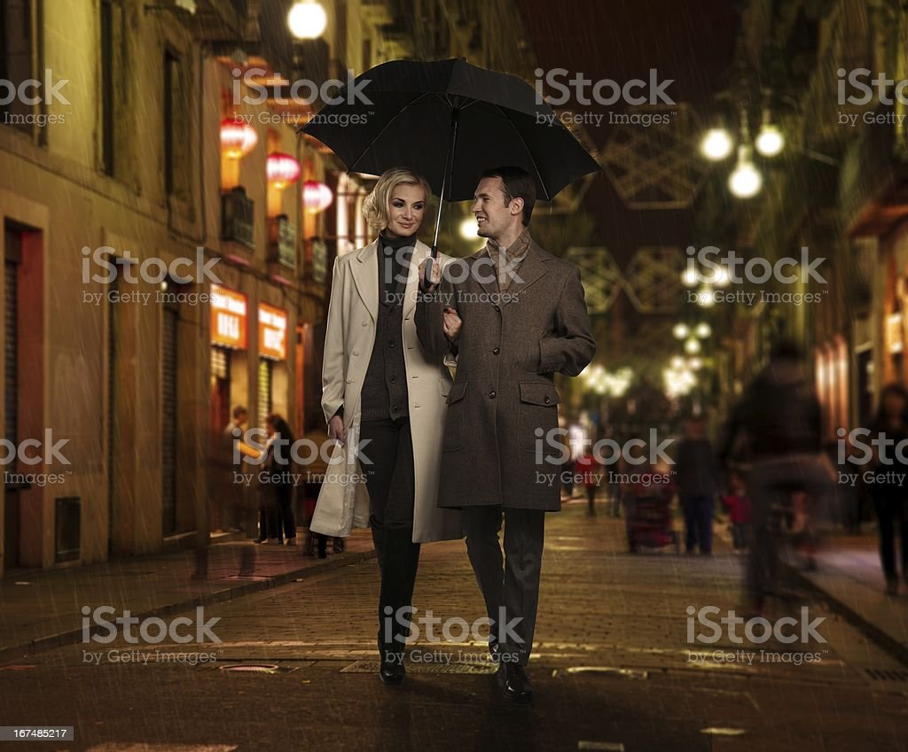 Elegant couple with umbrella outdoors on rainy evening stock photo