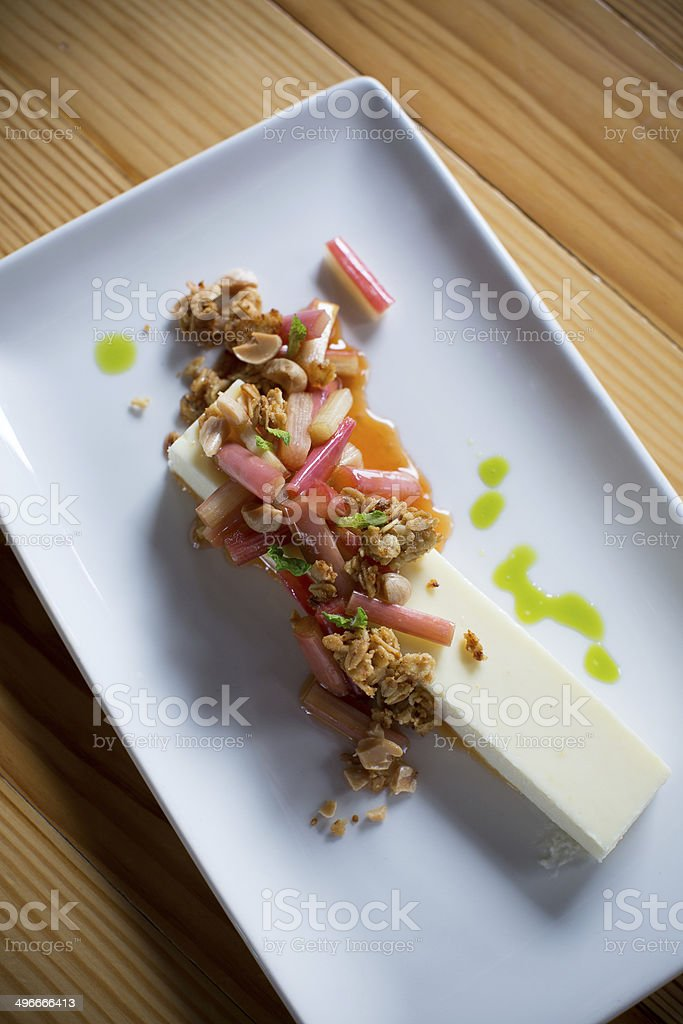 Elegant dessert - cheesecake, granola, rhubard and herb topping royalty-free stock photo