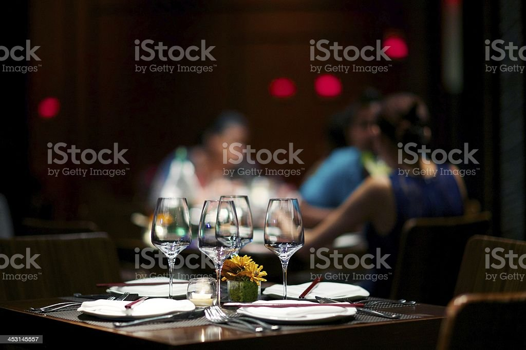 Elegant dining table with people in the background royalty-free stock photo