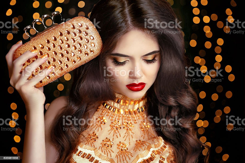 Elegant fashion brunette woman in gold. Wavy hair style. stock photo