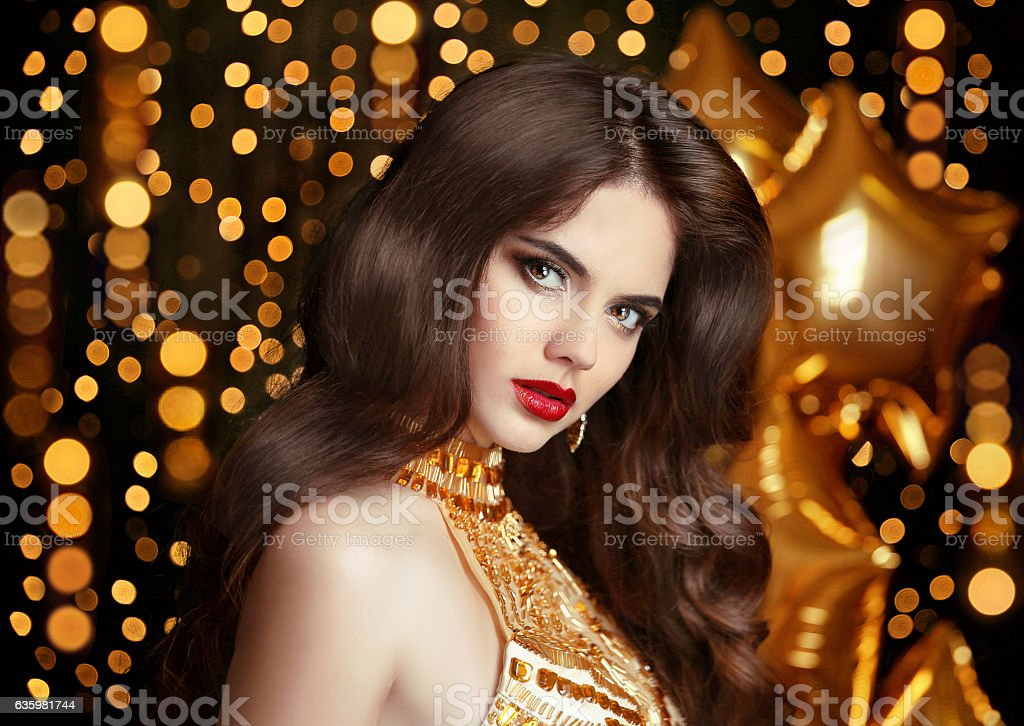 Elegant fashion brunette woman portrait in gold. Wavy hair style stock photo
